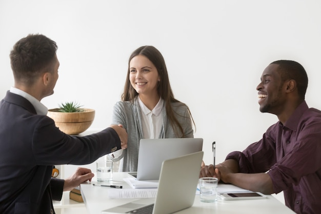 Donna di affari sorridente che stringe mano del socio maschio alla riunione di gruppo Foto Gratuite