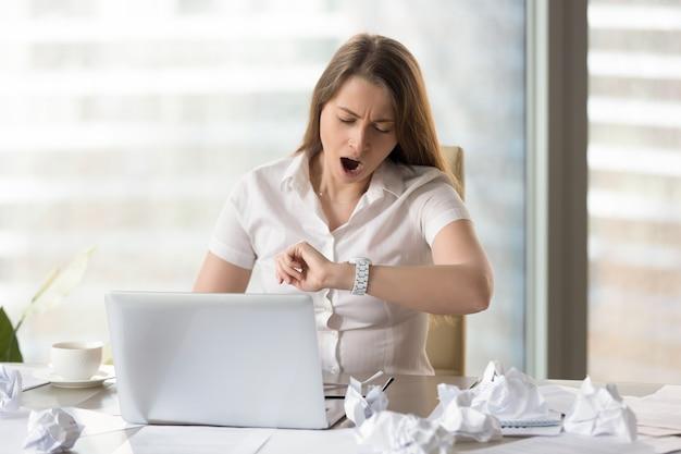 Donna di affari stanca che aspetta conclusione del giorno lavorativo Foto Gratuite
