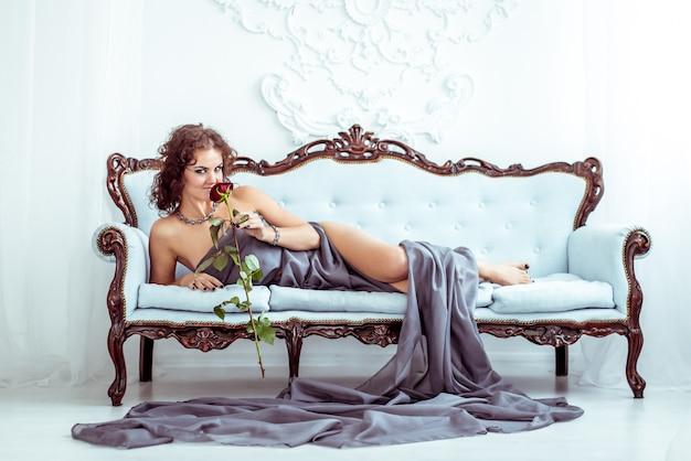 Donna di beautifu che si trova sullo strato e che tiene rosa rossa Foto Premium