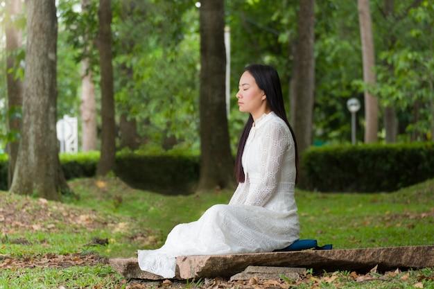 Donna di bellezza che medita nel giardino. Foto Premium
