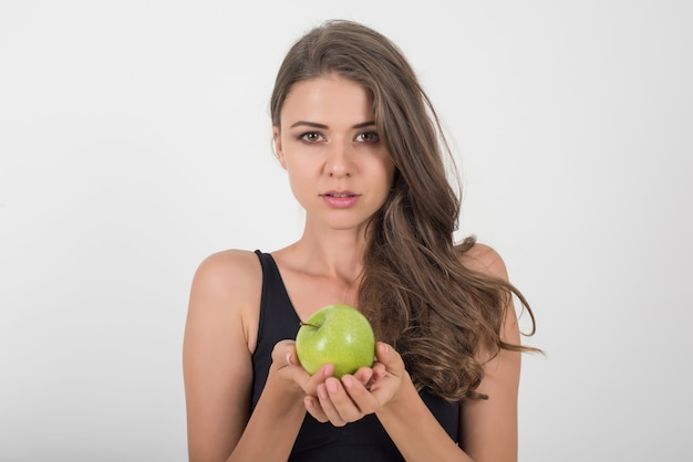 Donna di bellezza che tiene mela verde mentre isolato su bianco Foto Gratuite