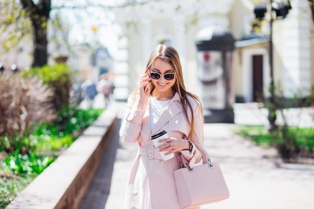 Donna di classe superiore. donna alla moda che manda un sms all'aperto. adatti la donna in occhiali da sole e una giacca rosa con caffè Foto Premium