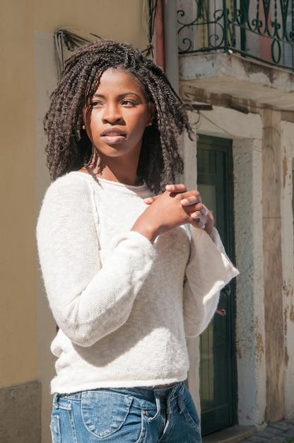 Donna di colore abbastanza giovane pensierosa che sta all'aperto Foto Gratuite