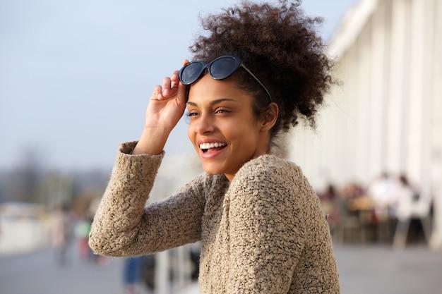 Donna di colore attraente che sorride all'aperto Foto Premium