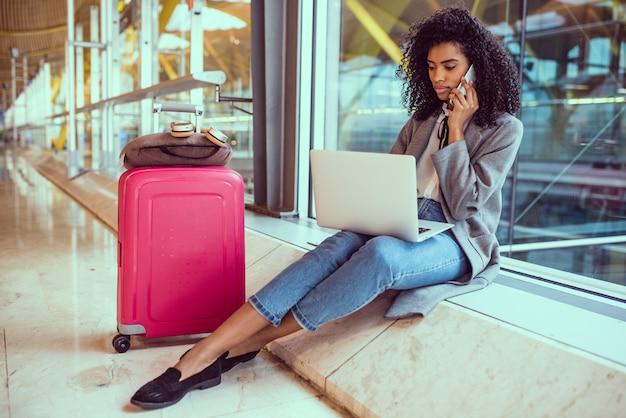 Donna di colore che per mezzo del telefono cellulare e del computer portatile all'aeroporto che si siede alla finestra Foto Premium