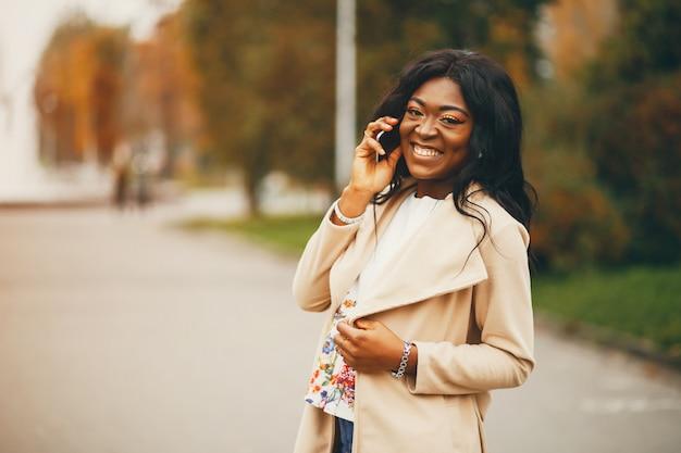 Donna di colore che si leva in piedi in una città di autunno Foto Gratuite