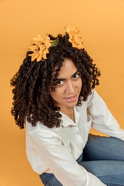 Donna di colore che si siede con i fiori nei capelli ...