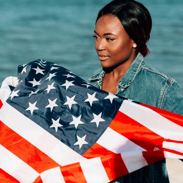Donna di colore che sta e che tiene bandiera americana Foto Gratuite