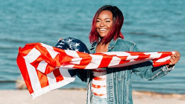 Donna di colore che tiene bandiera americana che fluttua nel vento Foto Gratuite