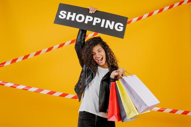 Donna di colore con il segno di acquisto e sacchetti della spesa variopinti isolati sopra giallo con nastro adesivo Foto Premium
