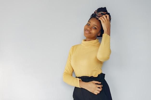Donna di colore sveglia che sta su una parete bianca Foto Gratuite