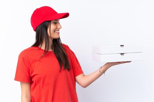 Donna di consegna della pizza che tiene una pizza sopra la parete bianca con l'espressione felice Foto Premium