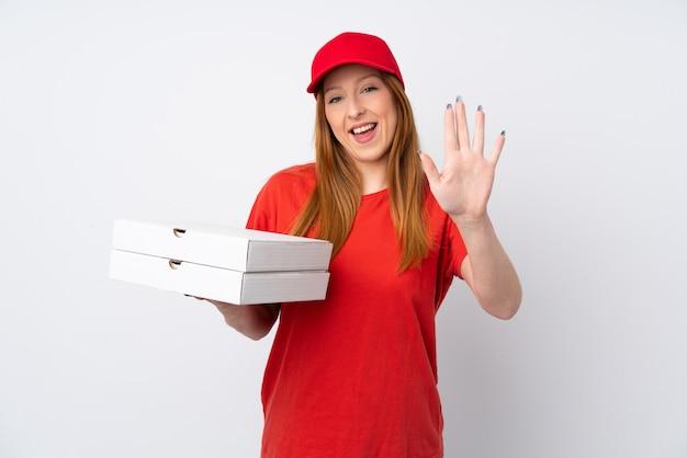 Donna di consegna della pizza che tiene una pizza sopra la parete rosa che saluta con la mano con l'espressione felice Foto Premium