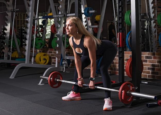 Donna di forma fisica che fa esercizio deadlift in palestra Foto Premium