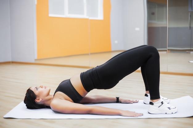 Donna di forma fisica che fa le esercitazioni sulla vista superiore della stampa. allenamento ragazza carina in palestra Foto Premium