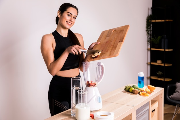 Donna di forma fisica che prepara un succo della disintossicazione Foto Gratuite