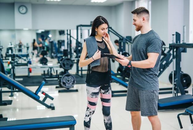 Donna di forma fisica che si esercita con l'istruttore di forma fisica in palestra. Foto Premium