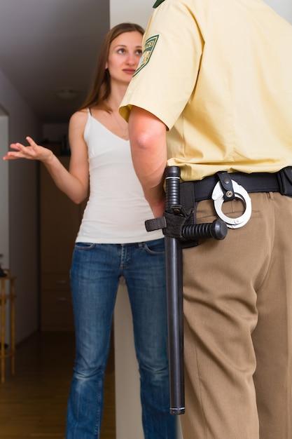 Donna di interrogatorio dell'ufficiale di polizia all'entrata principale Foto Premium