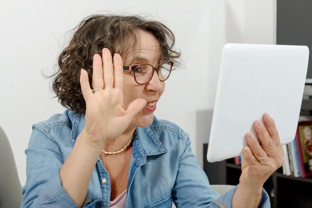 Donna di mezza età che fa una chiamata distante su internet Foto Premium