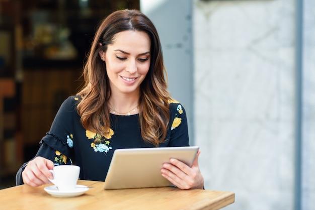 Donna di mezza età che utilizza compressa sulla pausa caffè nella barra urbana del caffè Foto Premium