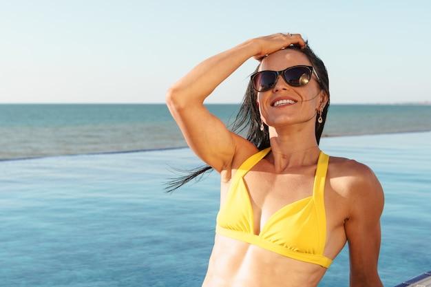 Donna di mezza età in bikini giallo che si siede vicino allo stagno Foto Premium