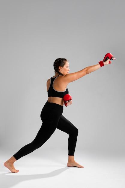 Donna di movimento di karatè che perfora con i guanti della scatola Foto Gratuite