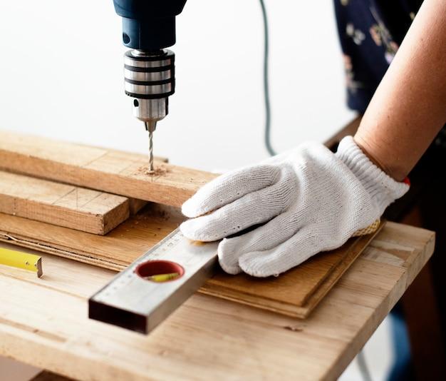 Donna di perforazione in una tavola di legno Foto Gratuite