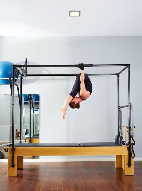 Donna di pilates in cadillac acrobatico sottosopra Foto Premium