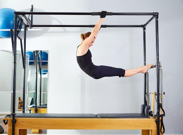 Donna di pilates in riformatore acrobatico della cadillac Foto Premium