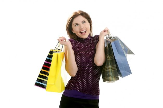 Donna di shopaholic con i sacchetti variopinti sopra bianco Foto Premium