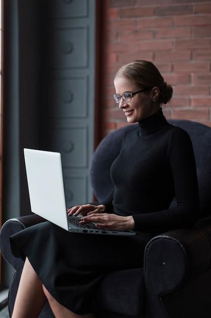 Donna di smiley che lavora al computer portatile Foto Gratuite