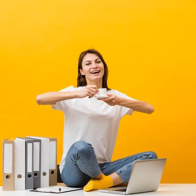 Donna di smiley che si siede sullo scrittorio e che gode della sua tazza di caffè Foto Gratuite