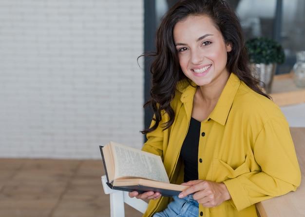 Donna di smiley con il libro che guarda l'obbiettivo Foto Gratuite