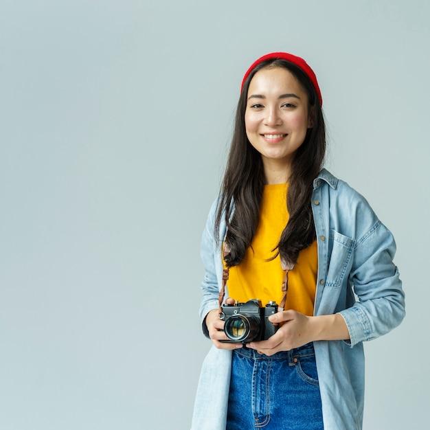 Donna di smiley con la macchina fotografica all'interno Foto Gratuite