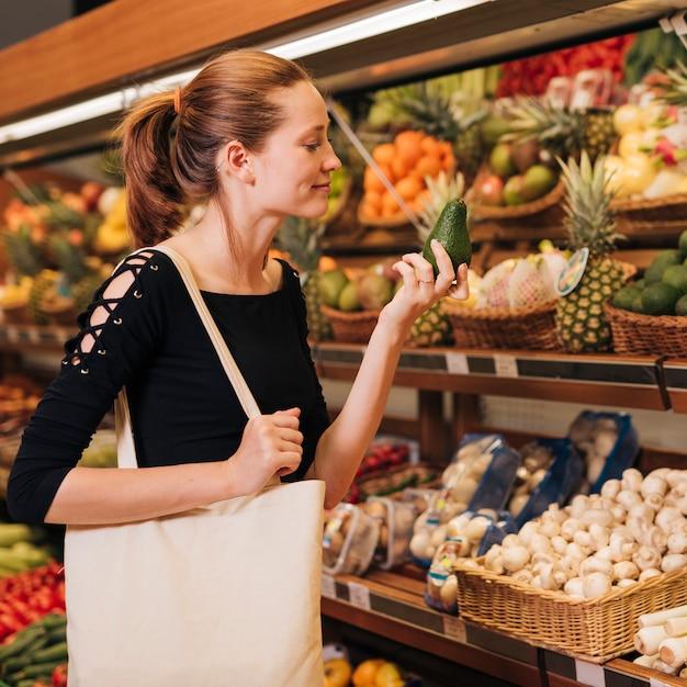 Donna di smiley del colpo medio che tiene un avocado Foto Gratuite