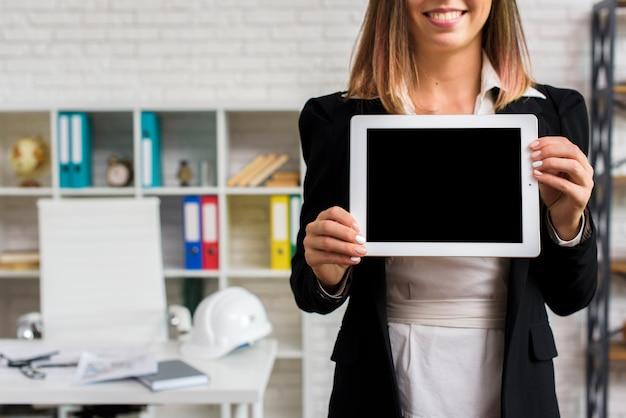 Donna di smiley in possesso di un modello di tablet Foto Gratuite