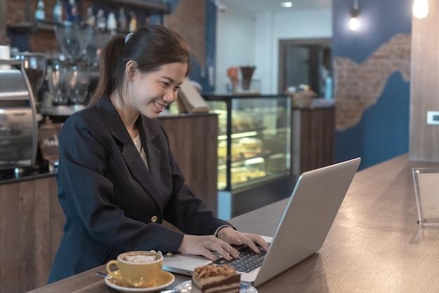 Donna di sorriso che esamina computer portatile e carta millimetrata con energicamente in caffetteria Foto Premium