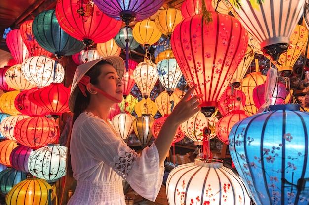 Donna di viaggio che sceglie le lanterne in hoi an, vietnam Foto Premium