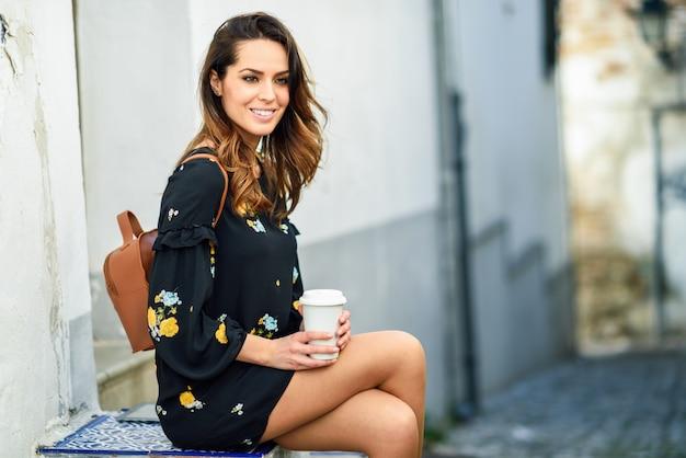 Donna di viaggio di mezza età che si siede mentre bevendo un certo caffè. Foto Premium
