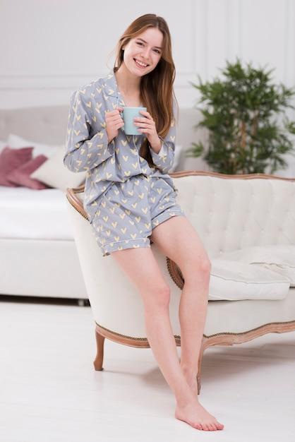 Donna di vista frontale a casa con la tazza di tè Foto Gratuite