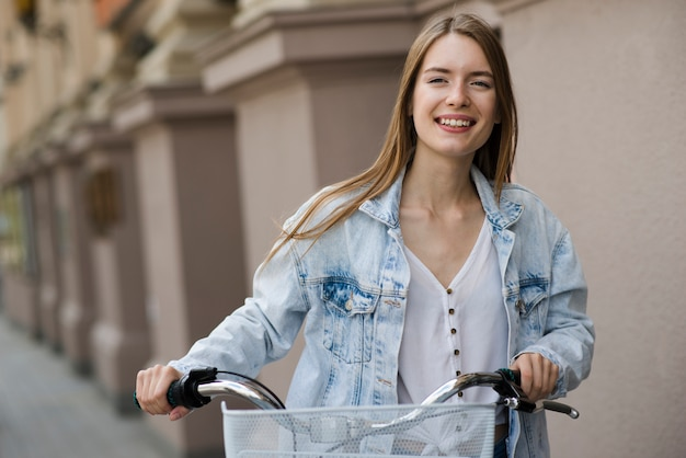 Donna di vista frontale che cammina accanto alla bici Foto Gratuite