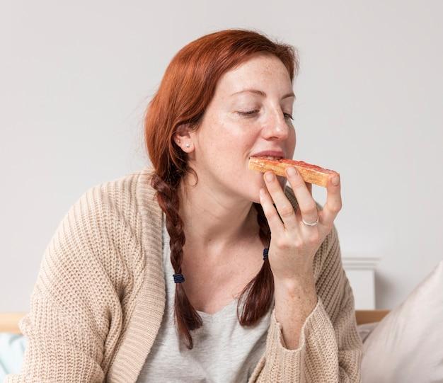 Donna di vista frontale che mangia prima colazione deliziosa Foto Gratuite