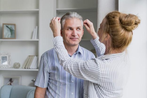 Donna di vista frontale che organizza i capelli dei mariti Foto Gratuite