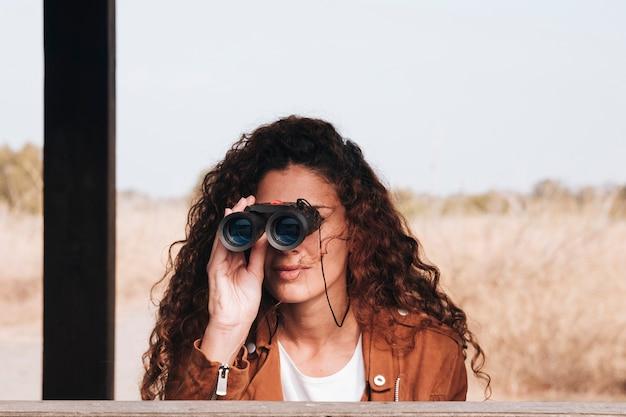 Donna di vista frontale che osserva tramite il binocolo Foto Gratuite