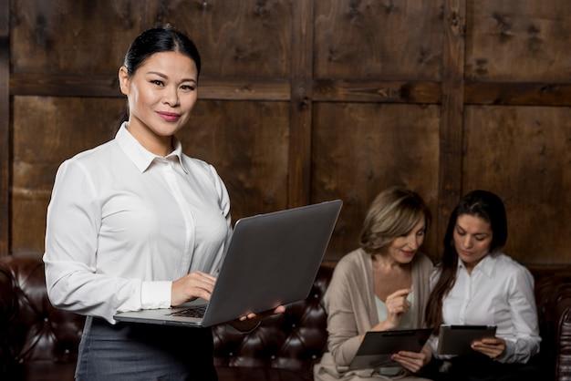 Donna di vista frontale con il computer portatile alla riunione Foto Gratuite