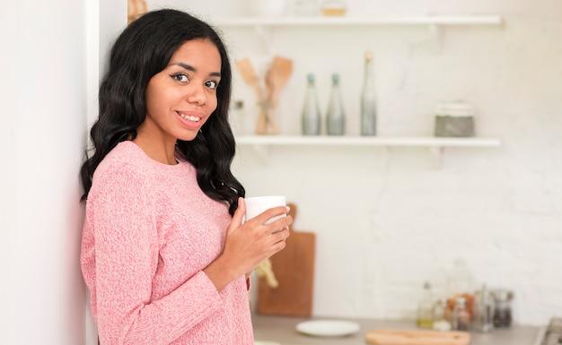 Donna di vista laterale a casa che beve caffè Foto Gratuite