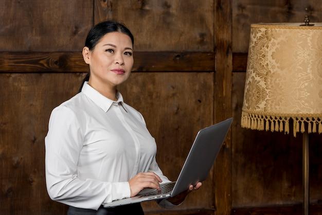 Donna di vista laterale che lavora al computer portatile Foto Gratuite