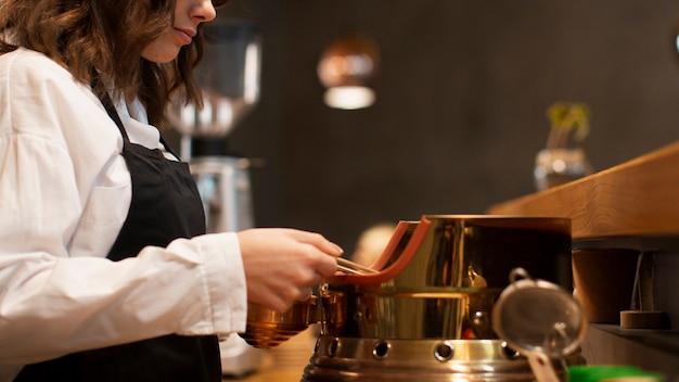 Donna di vista laterale che lavora nella caffetteria Foto Gratuite