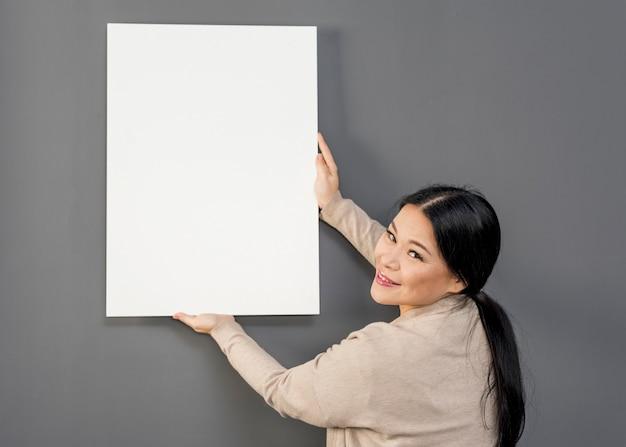 Donna di vista laterale che mette sullo strato della carta del balnk della parete Foto Gratuite