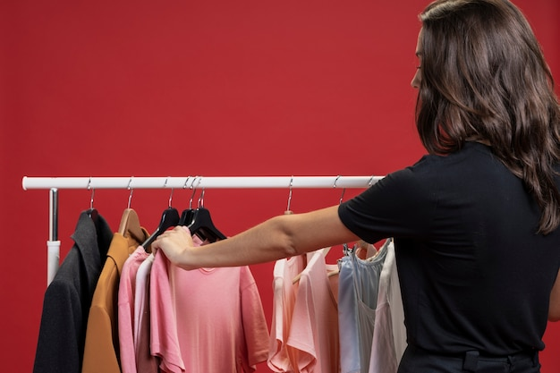 Donna di vista laterale che osserva attraverso le magliette Foto Gratuite